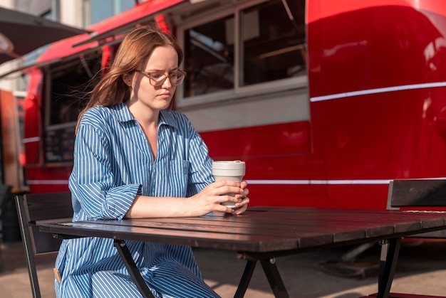 Young woman sitting alone with collapsible eco coffee cup near street food truck city lifestyle