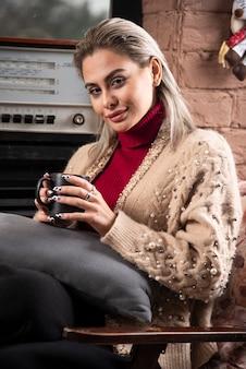 Молодая женщина сидит и держит горячий чай
