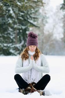 冬に公園で座って瞑想する若い女性