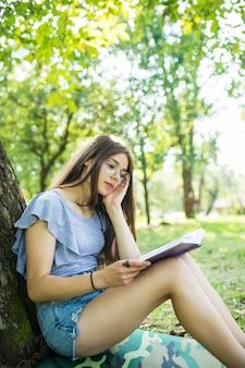 Молодая женщина сидит и читает свою любимую книгу на зеленой траве под деревом в приятное солнечное лето