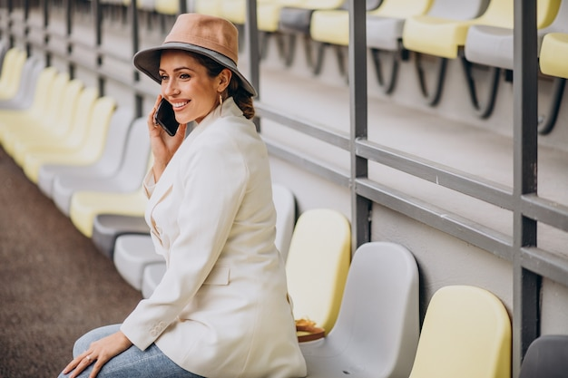Young woman sitting on arena seats and talking on the phone