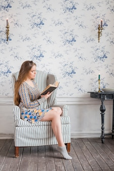 Young woman sitting on arm chair against wallpaper reading book
