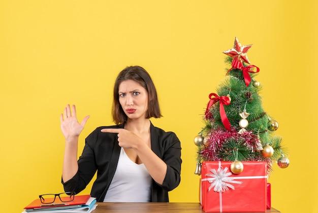 テーブルに座って、黄色のオフィスで飾られたクリスマスツリーの近くにスーツを着て手を指している若い女性