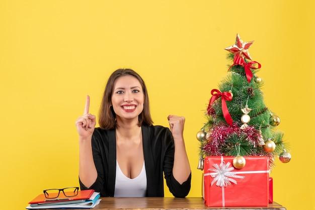 젊은 여자가 테이블에 앉아 노란색 사무실에서 장식 된 크리스마스 트리 근처 정장을 자랑스럽게 가리키는