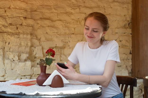 カフェのテーブルに座っている若い女性と電話を続けています。友達とモバイルチャット。
