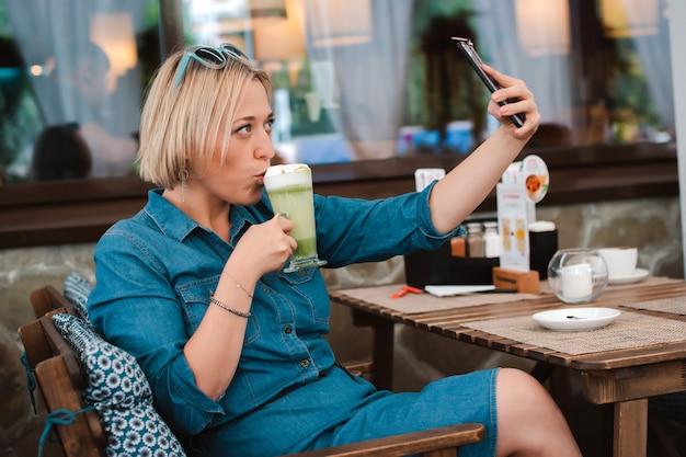테이블 여름 카페에 앉아 녹색 말차 음료를 마시고 셀카를하는 젊은 여자