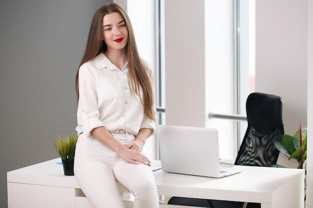 Молодая женщина, сидя за столом с ноутбуком в белом офисе. студент или бизнесвумен.