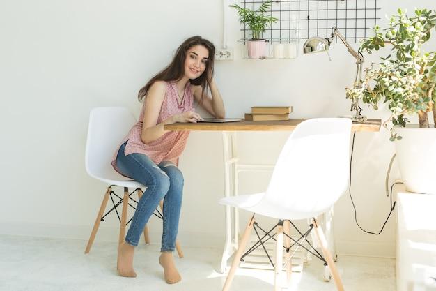 룸에서 타블렛으로 테이블에 앉아 젊은 여자