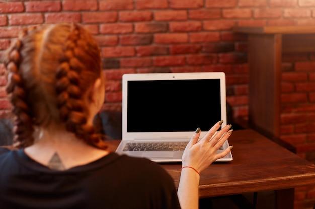노트북으로 카페에 앉아 젊은 여자