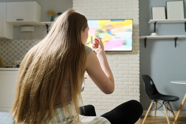 Молодая женщина сидит дома, смотрит телевизор и ест
