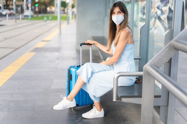 Молодая женщина, сидя на станции метро или трамвая в ожидании общественного транспорта