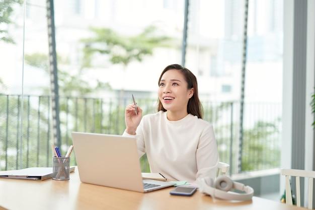 ノートパソコンでオフィスのテーブルに座っている若い女性
