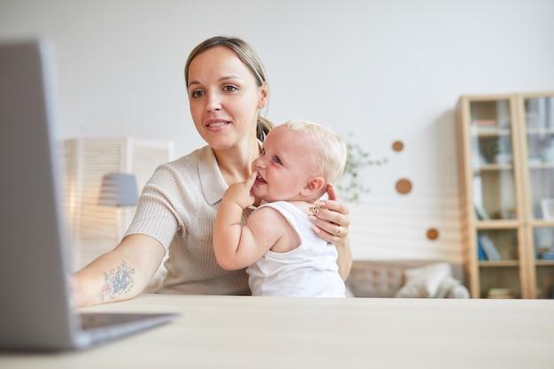 Молодая женщина сидит за столом, серфинг в интернете на ноутбуке, пока ее ребенок сидит у нее на коленях