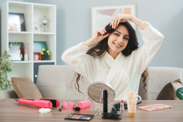 化粧ツールとテーブルに座っている若い女性は、リビングルームのカーラーで髪を巻く