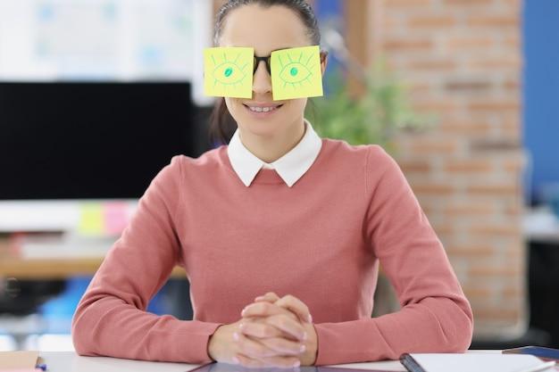 안경에 스티커를 붙인 테이블에 앉아 있는 젊은 여성. 작업 개념에서 게으름