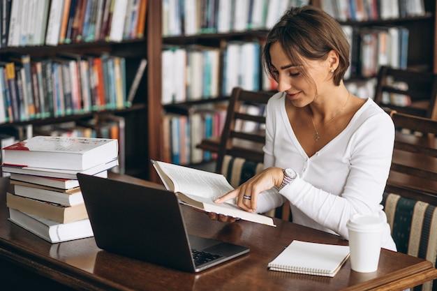 Молодая женщина, сидя в библиотеке с помощью книг и компьютера