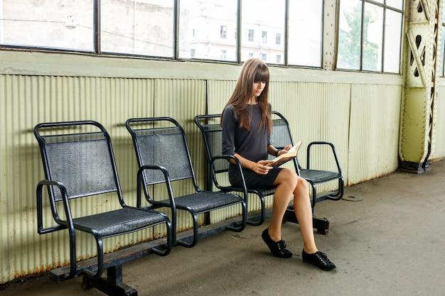 책을 읽고 역에 앉아 젊은 여자.