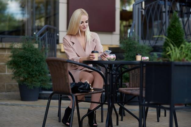 Молодая женщина, сидящая в уличном кафе, пьет кофе и использует мобильный телефон