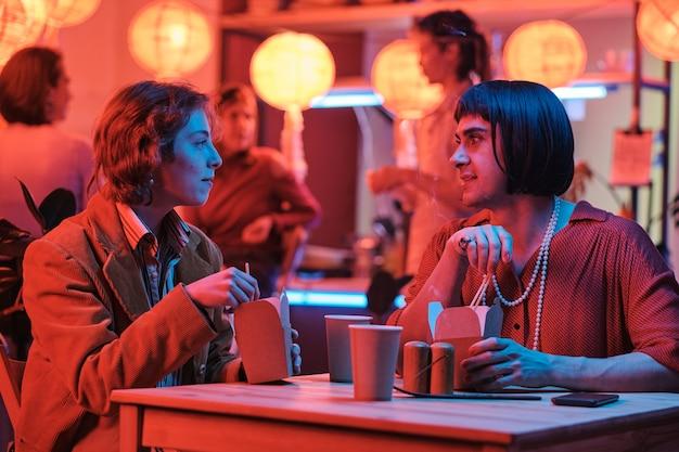 テーブルに座って、バーで彼女のゲイの友人と一緒に食べ物を食べる若い女性