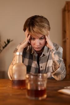 젊은 여자가 테이블에 앉아 위스키 병을보고 그녀는 술에 취해 알코올 중독이 있습니다.