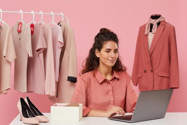 テーブルに座ってラップトップを使用して彼女がオンラインで服を買う若い女性