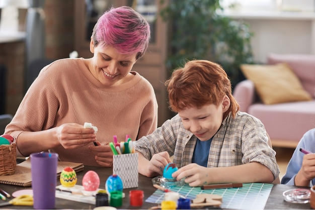 젊은 여자는 소년과 함께 테이블에 앉아 부활절을 위해 페인트로 계란을 칠합니다.