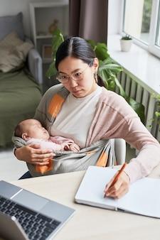 Молодая женщина сидит за столом с ребенком на руках и учится дома во время декретного отпуска