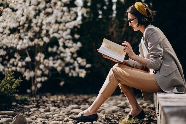 Giovane donna che si siede nel cortile e libro di lettura