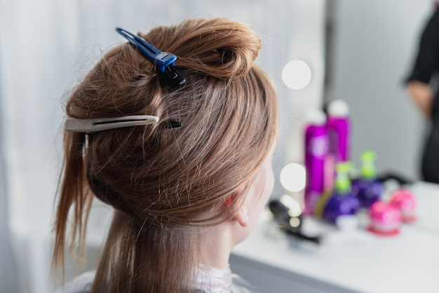 Young woman sitting in beauty hair salon style and waiting for hairdresser to make hairdo