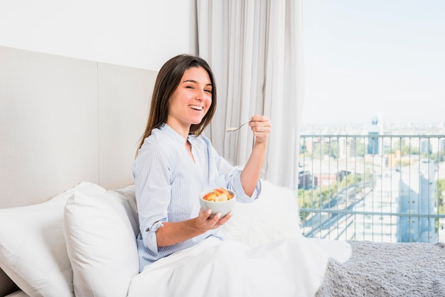 Young woman sitting on bed enjoying the fruit salad