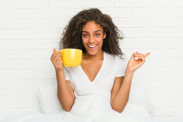 Young woman sitting on the bed holding a coffee mug smiling cheerfully pointing with forefinger away