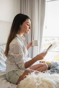 Young woman sitting on bed reading newspaper while drinking coffee