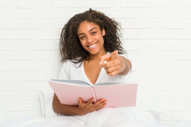Young woman sitting on the bed studying cheerful smiles pointing to front