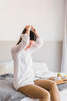 Young woman sitting on bed tying her hair