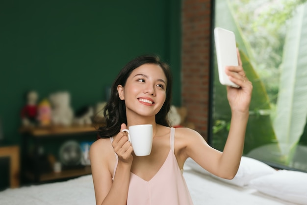 Young woman sitting on bed with cup of coffee selfie on mobile phone