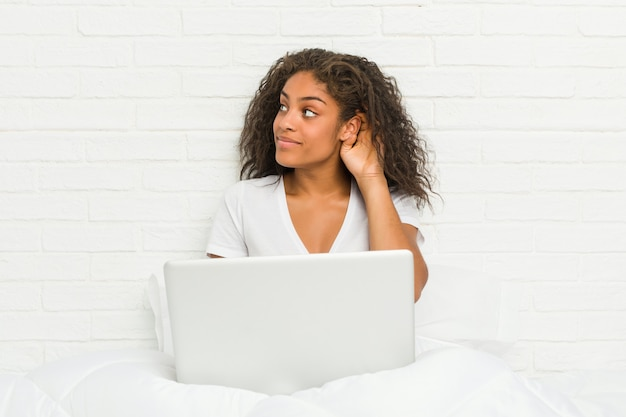 Young woman sitting on the bed with laptop trying to listening a gossip