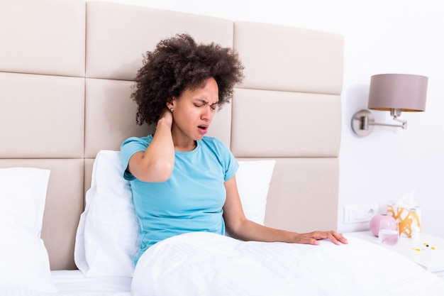 Young woman sitting on the bed with pain in neck touches her neck suffers from painful feelings ache caused by poor wrong posture, sedentary work, sitting for long period concept image