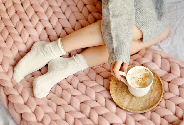 Young woman sitting on the bed with pink giant merino wool plaid blanket with cup of cappuccino.