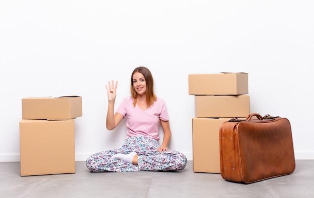 Молодая женщина, сидящая между коробками, улыбается и смотрит вежливо, показывая номер четыре или четвертый рукой вперед