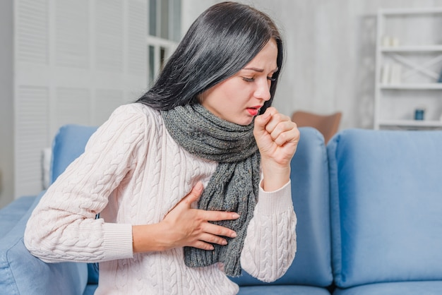 Young woman sitting on blue sofa suffering from couch having chest pain