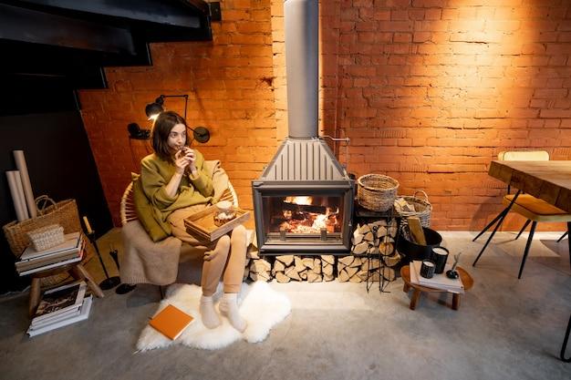 Молодая женщина сидит у горящего камина, расслабляясь с горячим напитком в уютном интерьере в стиле лофт в зимнее время
