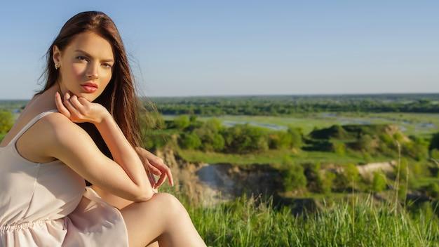 자연에 야외에서 절벽에 앉아 젊은 여자. 야외 포즈 흰 드레스와 매력적인 여자. 필드에서 포즈를 취하는 여성 모델은 화창한 여름 날.