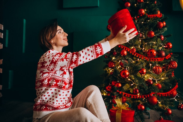 Young woman sitting by the christmas tree with red boxes