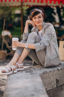 Young woman sitting by the fountain and drinking coffee