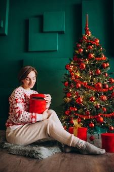 빨간 상자와 함께 크리스마스 트리 옆에 앉아 젊은 여자