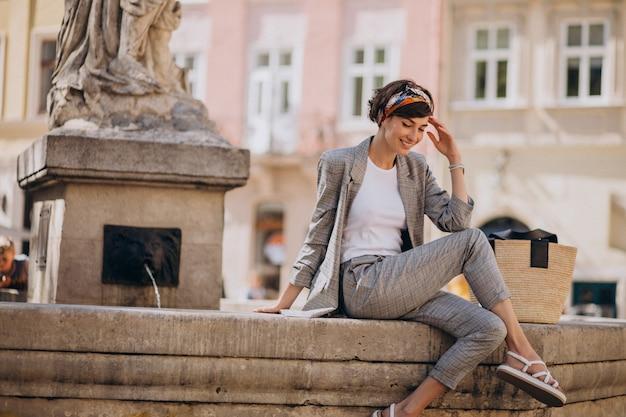 噴水のそばに座っている若い女性