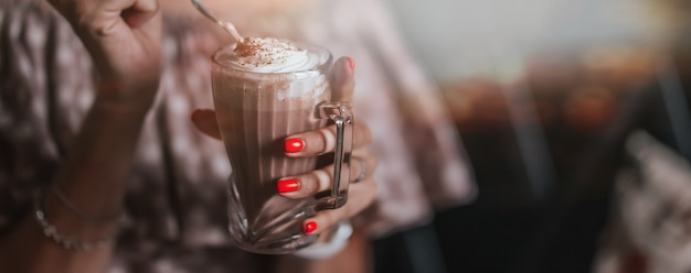 Young woman sitting in cafe holding spoon ang glass with coffee or milkshake with whipped cream