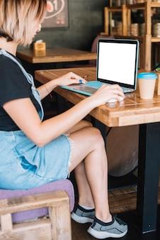 Giovane donna che si siede nel caffè usando portatile portatile