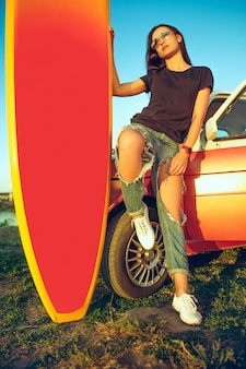 Young woman sitting on car with surfboard