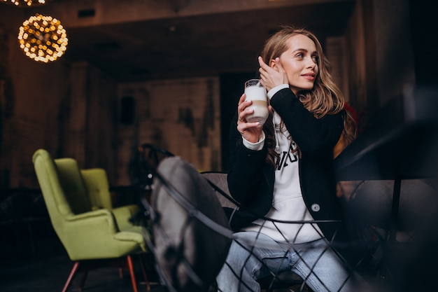 Young woman sitting in a chair inside a cafe